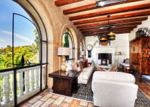 Exposed wooden beams textured walls and arched windows shape a stylish sunroom 217x155 Embracing Warmth: 25 Mediterranean Inspired Sunrooms for a Cozy Staycation