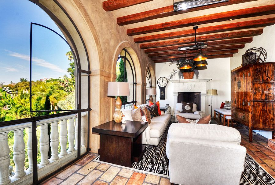 Exposed wooden beams, textured walls and arched windows shape a stylish sunroom