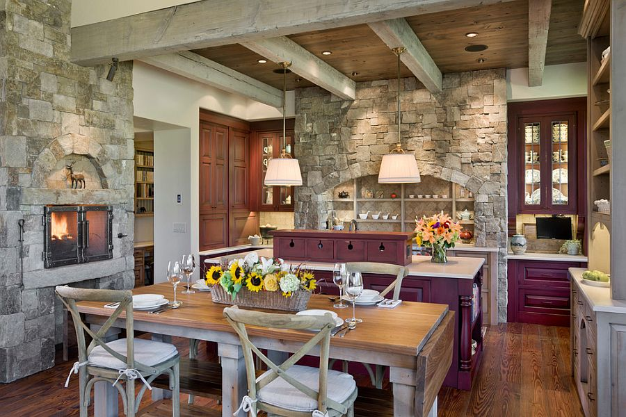 View in gallery Exquisite eat-in kitchen with fireplace, purple cabinets  and stone walls [Design: