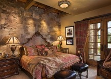 Exquisite rustic bedroom with stone wall has a masculine vibe