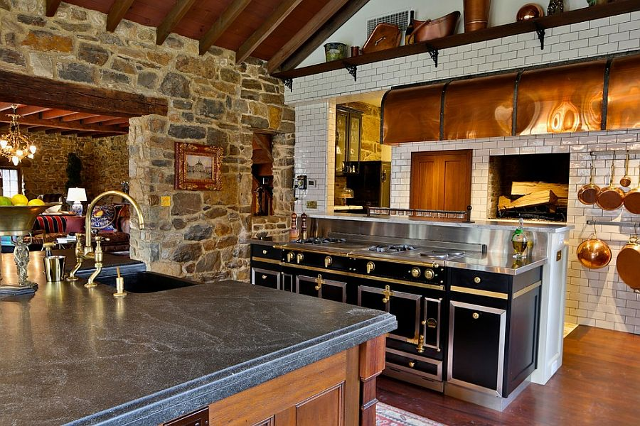 Farmhouse style kitchen with stone wall and La Cornue Range [Design: Squaresapace]