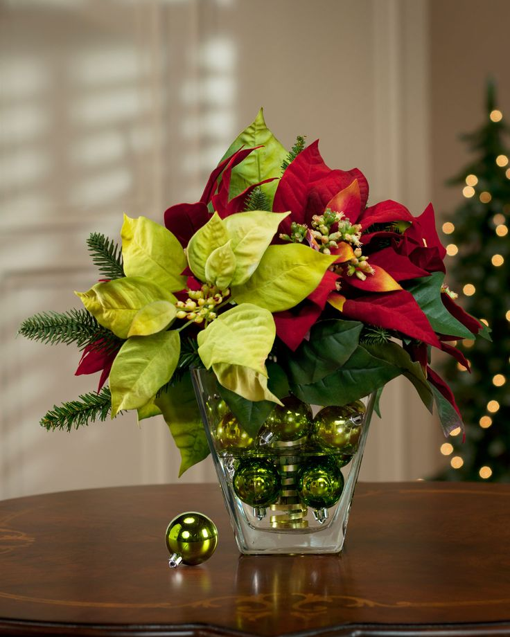 Faux poinsettia arrangement in glass vase with Christmas ball ornaments
