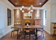 Glittering-globe-chandelier-stands-in-contrast-to-the-rustic-brick-background-in-the-dining-room-217x155