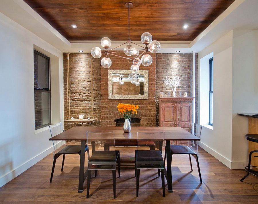 Glittering globe chandelier stands in contrast to the rustic, brick background in the dining room [Design: StudioLAB]