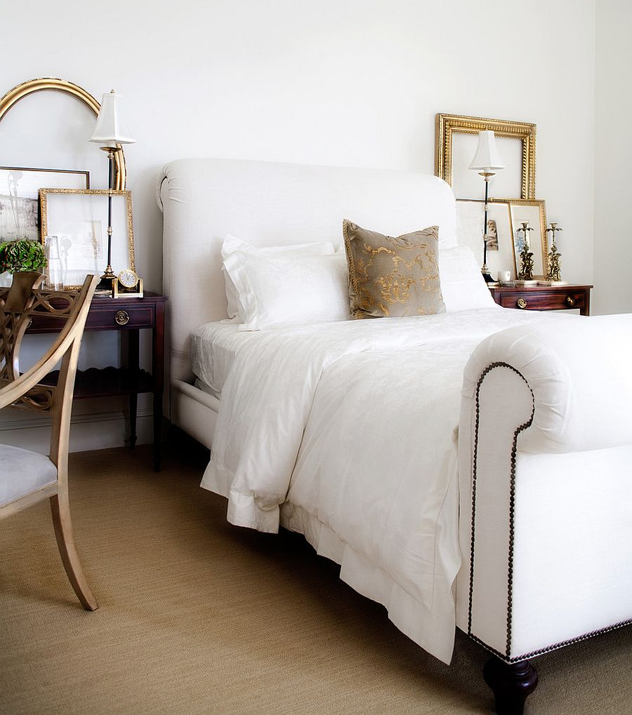 Gold frames bring sparkle and symmetry to this all-white bedroom [Design: Jessica Bennett Interiors]