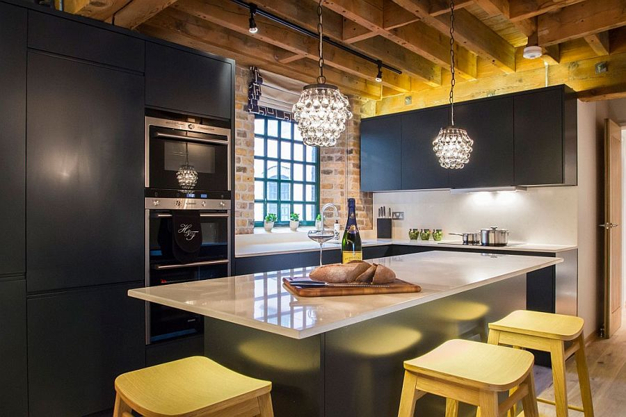 Gorgeous pendant lights add to the glitter of the bluish-gray kitchen with brick wall