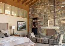 Imposing stone wall adds to the dramatic ambiance of the bedroom
