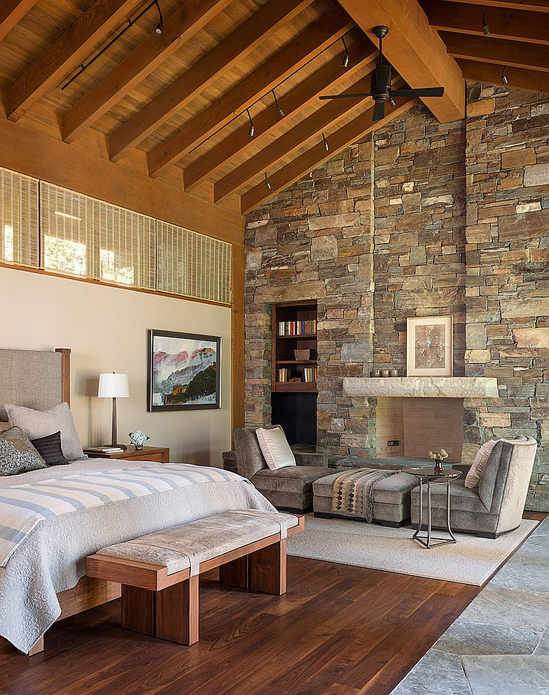 Imposing stone wall adds to the dramatic ambiance of the bedroom [Design: Gregory Carmichael Interior Design]