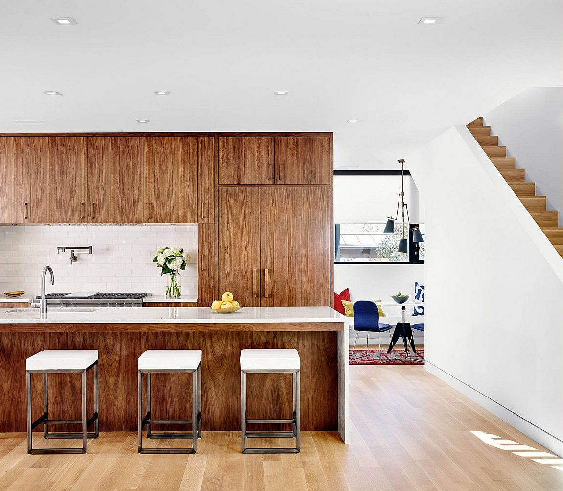 Kitchen draped in walnut veneer brings warmth to the modern interior