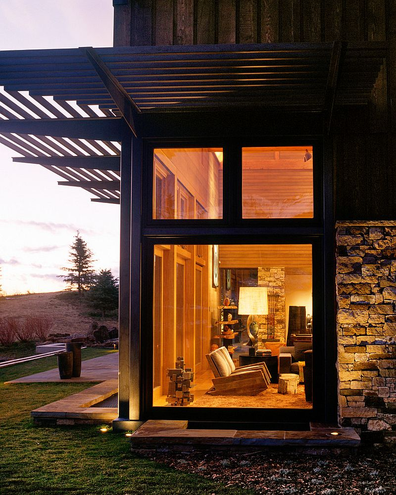 Large glass windows bring a dash of modernity to the stone and wood mountain home