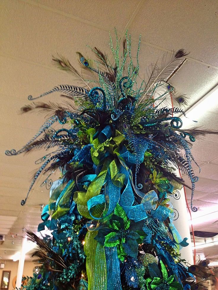 Large peacock-inspired tree topper with lots of blue and green ribbon