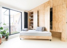 Living room couch that slides under the custom wooden unit 217x155 Tiny 28 Sqm Flat in Milan Wows with Flexible, Space Saving Design