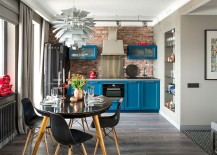 Lovely blue cabinets and bold black refrigerator enliven the industrial kitchen