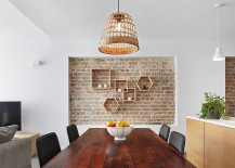 Lovely recessed brick wall in the dining room with geometric wooden shelves