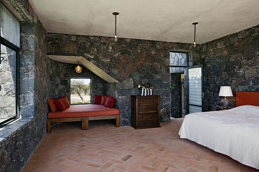 Mediterranean bedroom showcases terracotta tiles and dark stone walls [Design: David Howell Design]