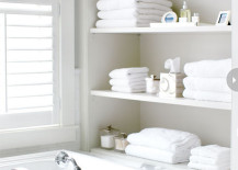 Open shelving at end of bathtub in white, chic bathroom