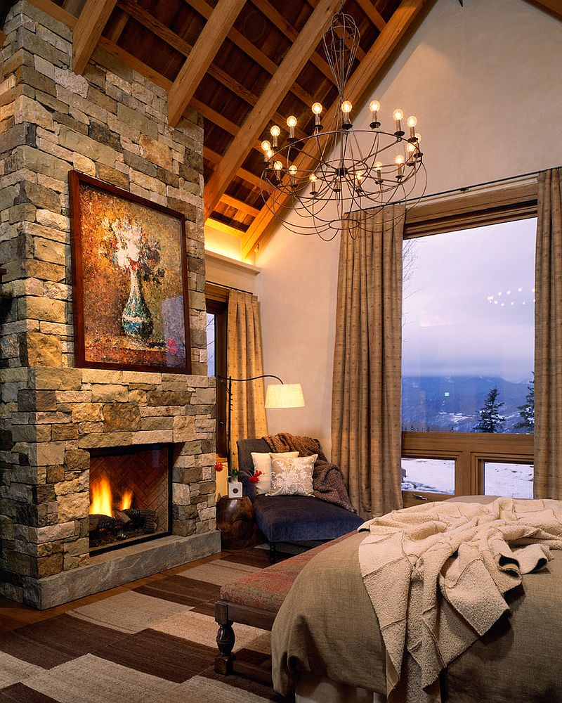 Rustic bedroom with cozy stone fireplace and mountain view