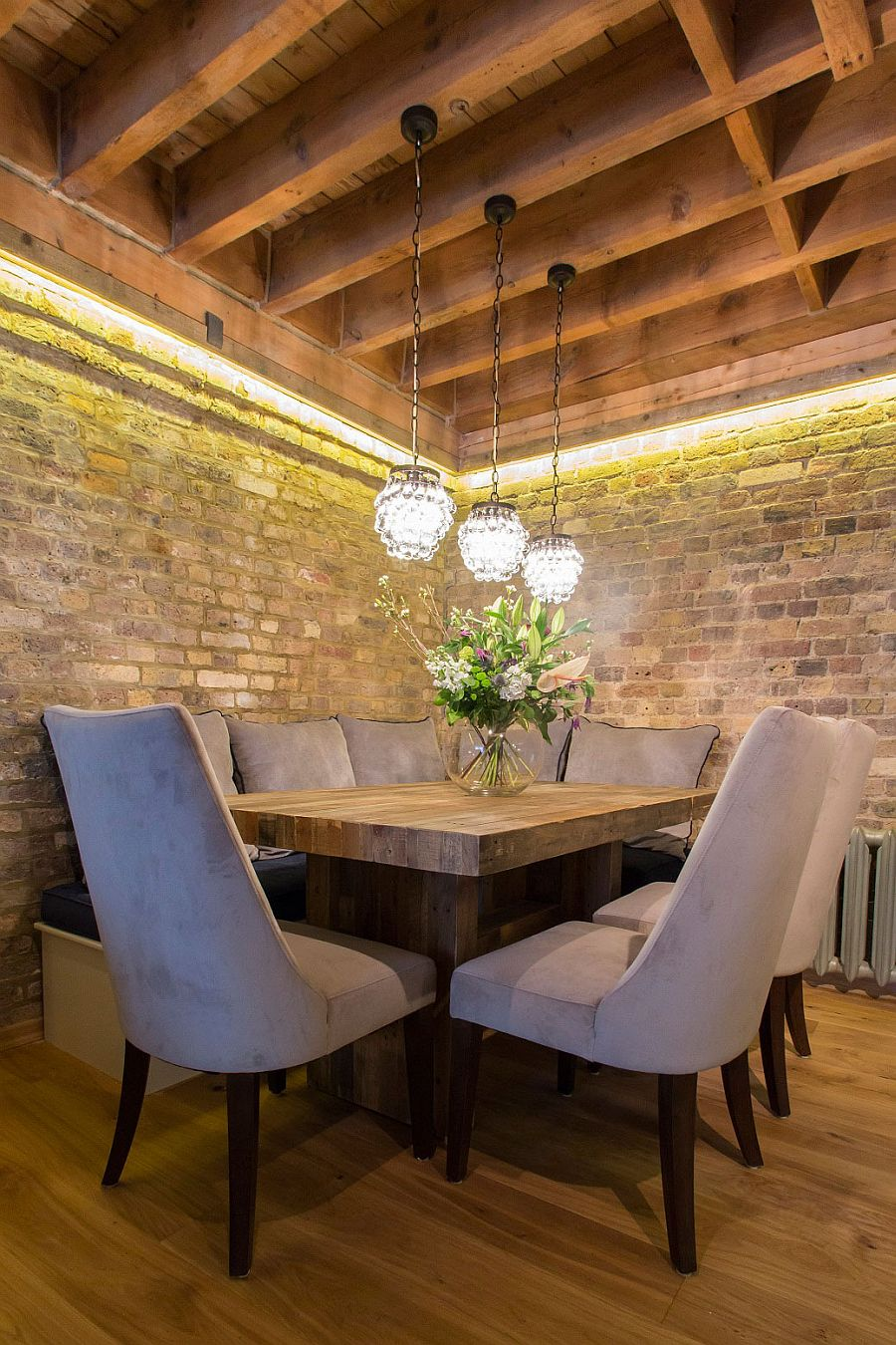 Rustic dining space with brick walls and custom wooden dining table