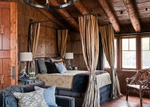 Rustic log cabin bedroom with a cozy canopy bed