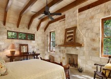 Rustic modern bedroom with exposed wooden beams and stone and mortar wall