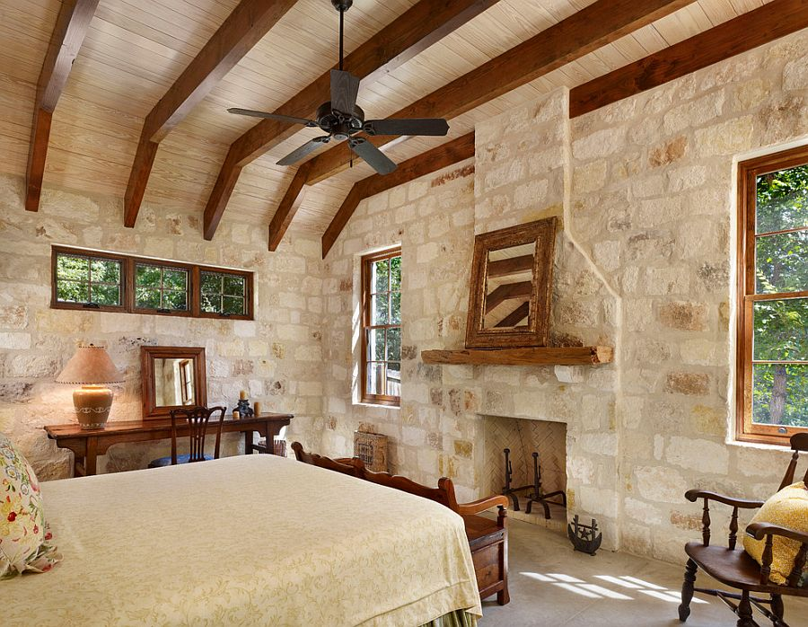 Rustic modern bedroom with exposed wooden beams and stone and mortar wall [Design: Northworks Architects and Planners]