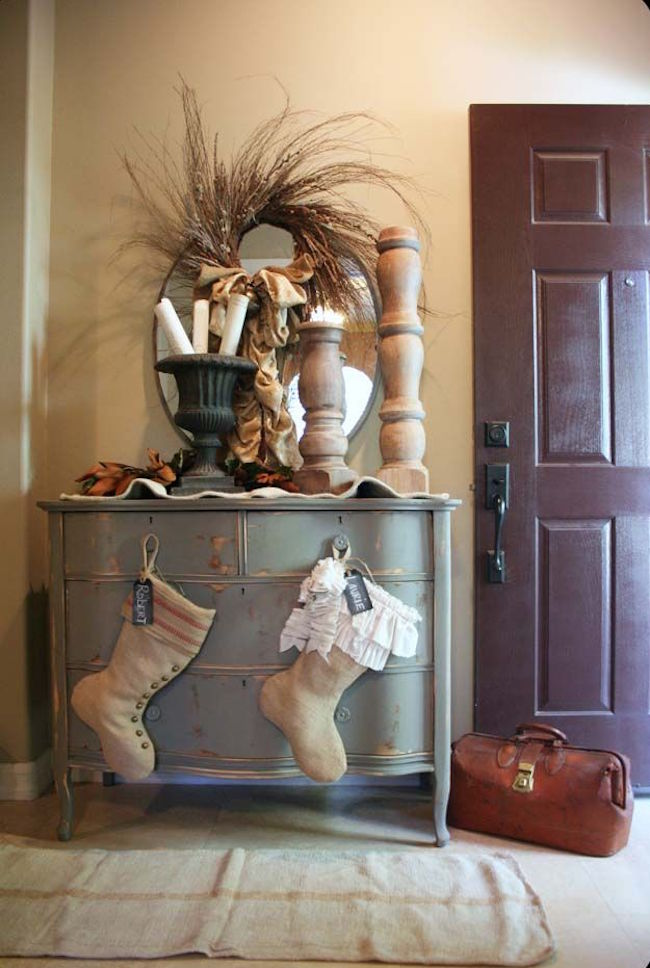 Rustic stockings hung on entryway dresser knobs