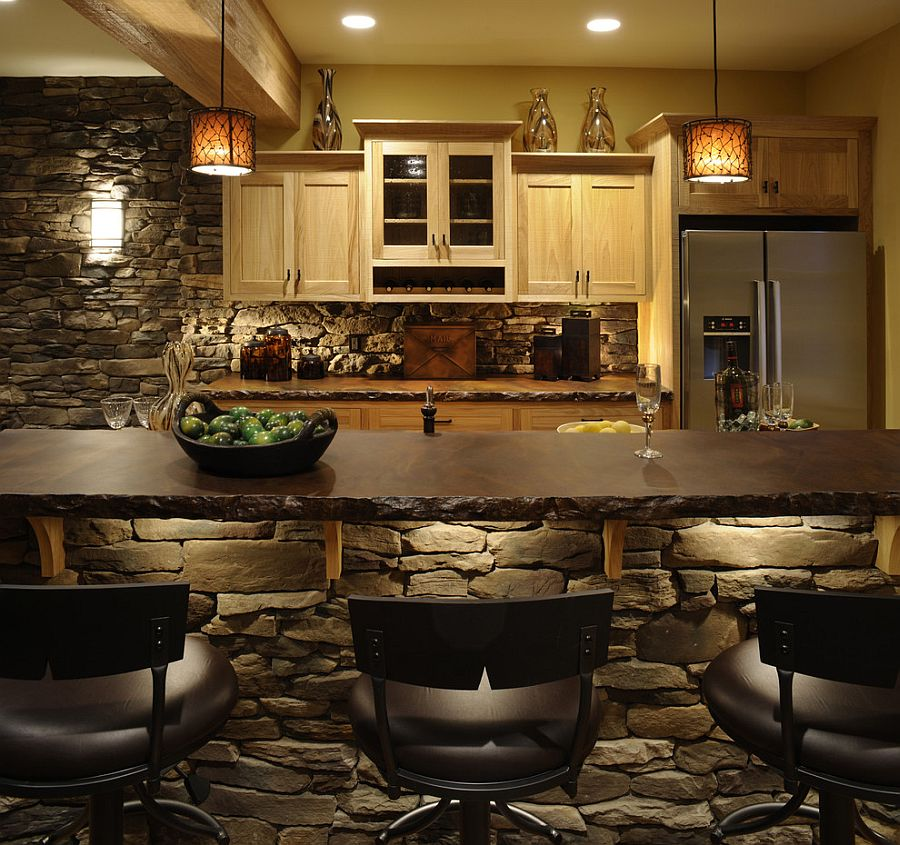 Simply stunning stone kitchen island with beautiful lighting that highlights its elegance [Design: Weaver Custom Homes]