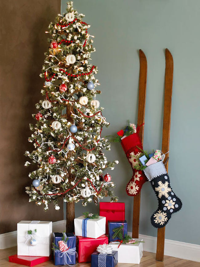 Skis with stockings hung on them next to Christmas tree