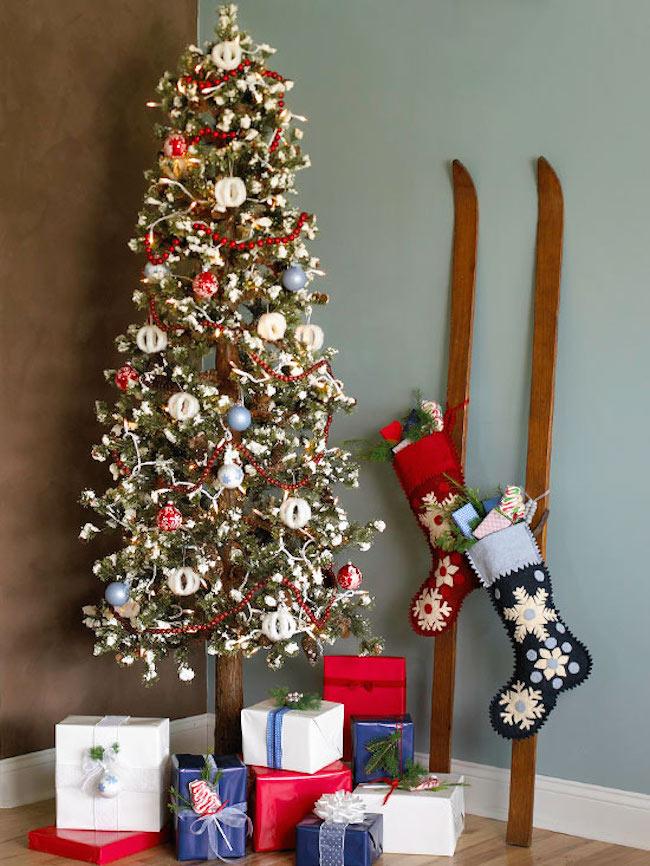 Skis with stockings hung on them next to Christmas tree