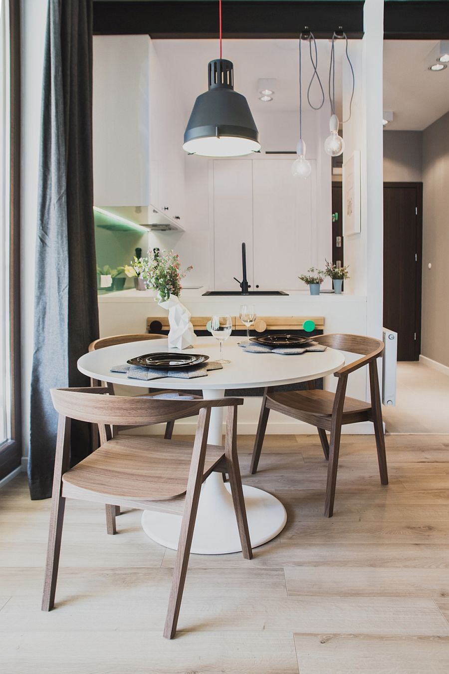 Small dining space for space-savvy apartment with round table and pendant light in gray