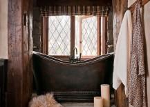 Small rustic bathroom with stone steps and a custom copper bathtub