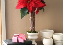 Some red poinsettias displayed with a collection of sticks 217x155 17 Lovely Ways to Display Poinsettias for the Holidays