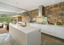 Stone wall connects the kitchen with the pool deck outside