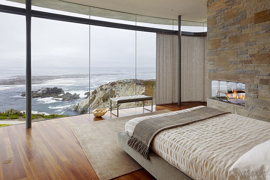 Stone wall in the contemporary bedroom complements the rugged landscape outside [From: Fulcrum Structural Engineering]