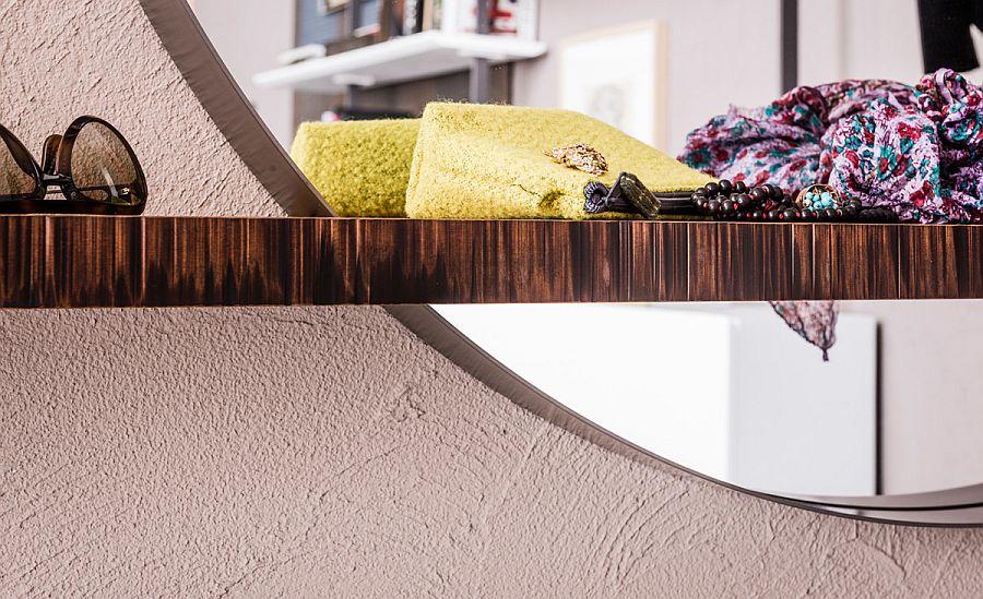Stylish combination of floating shelf and round mirror