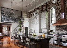 Sweeping Victorian kitchen with high ceiling, brick wall backdrop and an air of dramatic flair
