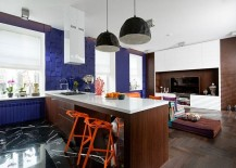 Textured wall with custom 3d Panels in blue and snazzy Konstantin Grcic orange chairs shape the eclectic apartment