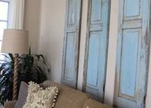 Three rustic blue shutters in a living room above a sofa 217x155 7 Inspiring Ways to Use Vintage Shutters on Your Walls