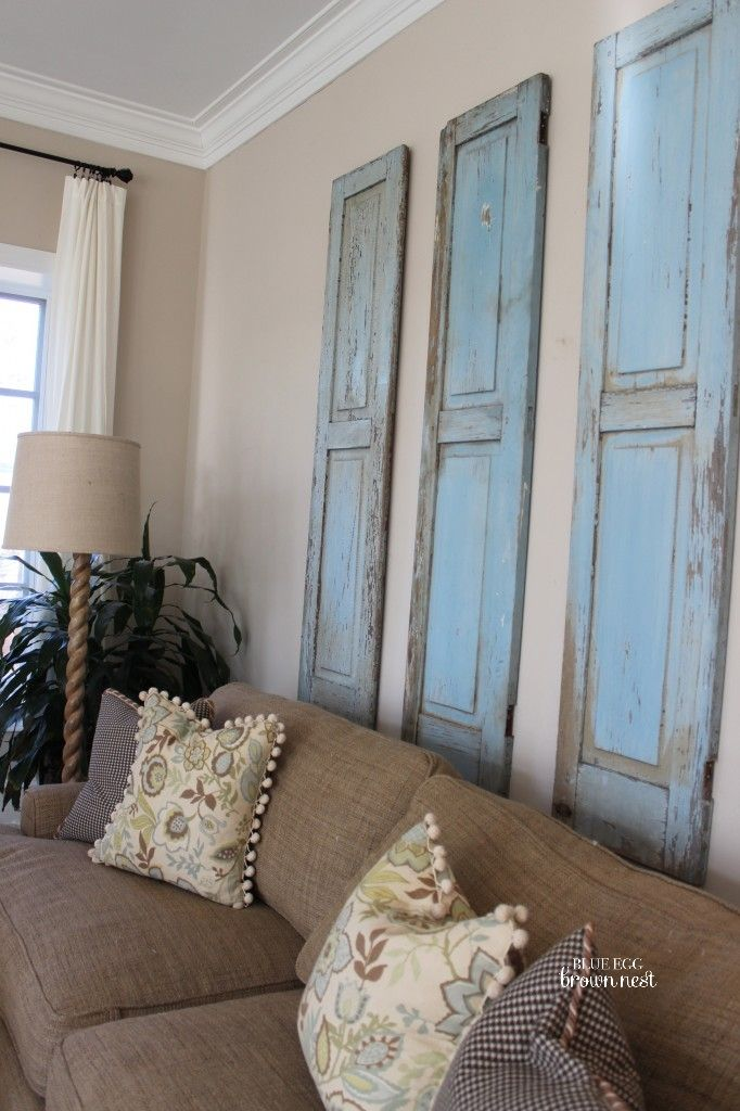 Three rustic blue shutters in a living room above a sofa