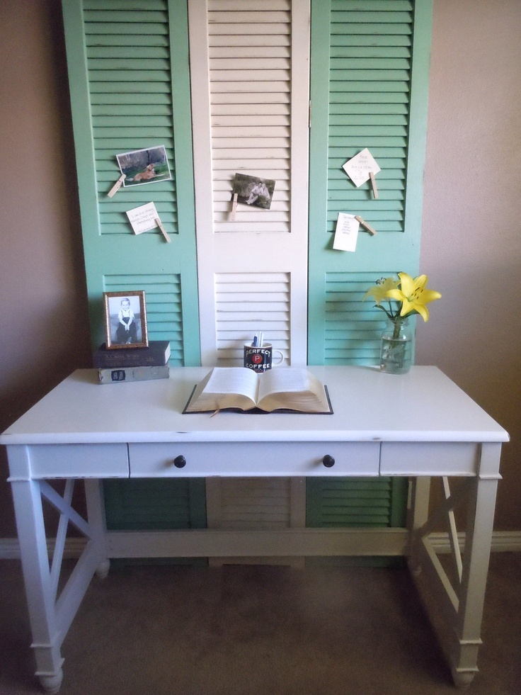 Three shutters used as a bulletin board in front of a desk