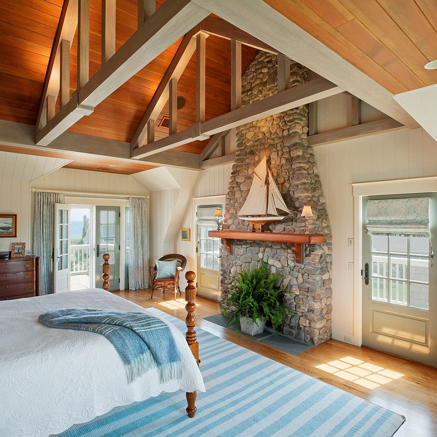 Traditional stone fireplace used as a decorative element in the beach style bedroom [Design: Dennis Moffitt Painting]