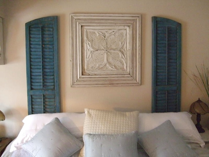 Vintage shutters and artwork used in place of a headboard