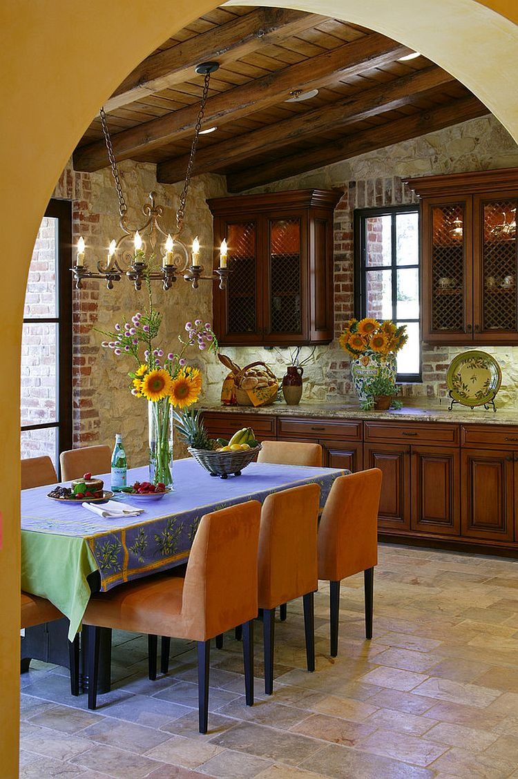 Walls clad in natural stone and brick veneer for the Mediterranean dining room [Design: Jon Eric Christner Architect]