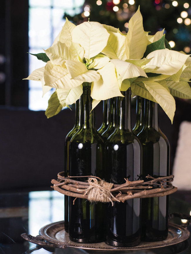 White poinsettias displayed in wine bottles