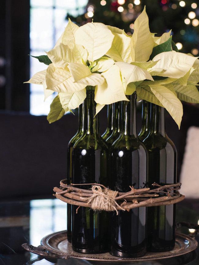 White poinsettias displayed in wine bottles
