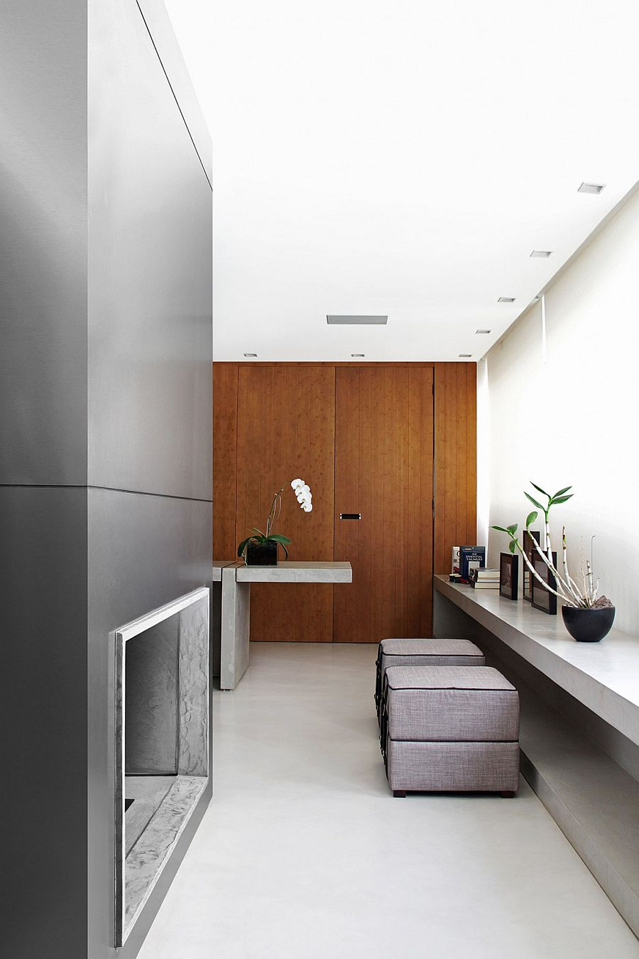 Wooden doors and wall surfaces bring warmth to the modern minimal home