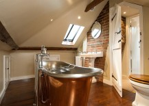 Attic bathroom with exposed brick wall and copper bathtub