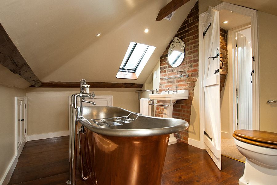 Attic bathroom with exposed brick wall and copper bathtub [Design: A1 Lofts and Extensions]