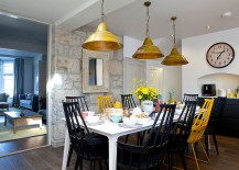 Beach style dining room with accent stone wall and colorful chairs