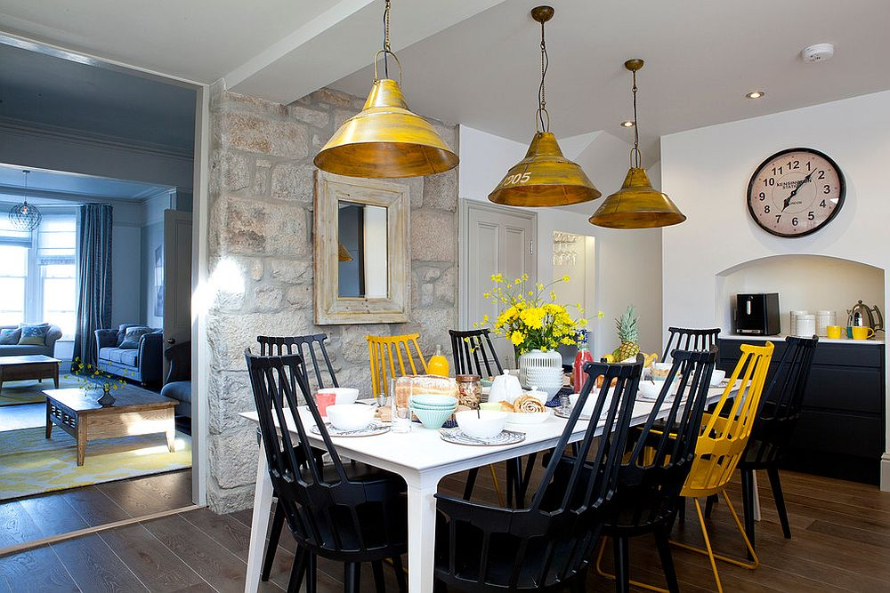 Beach style dining room with accent stone wall and colorful chairs [Design: Camellia Interiors]